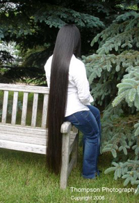 girl with extremely long hair sitting on a bench