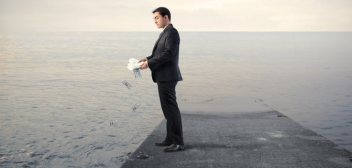 man throwing money into the sea