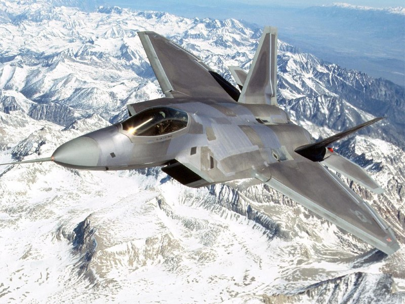 american Lockheed Martin F-22 Raptor flying over snowy mountains