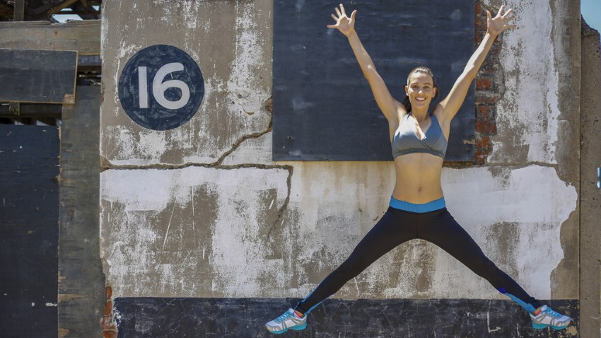 lady doing a star jump exercise in black leggings