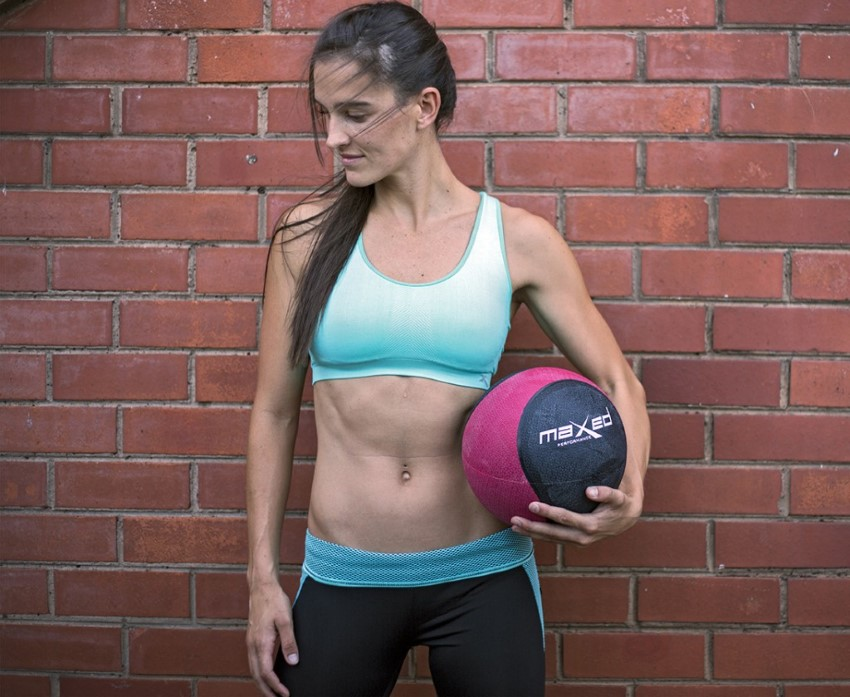 lady in exercise wear holding a medicine ball