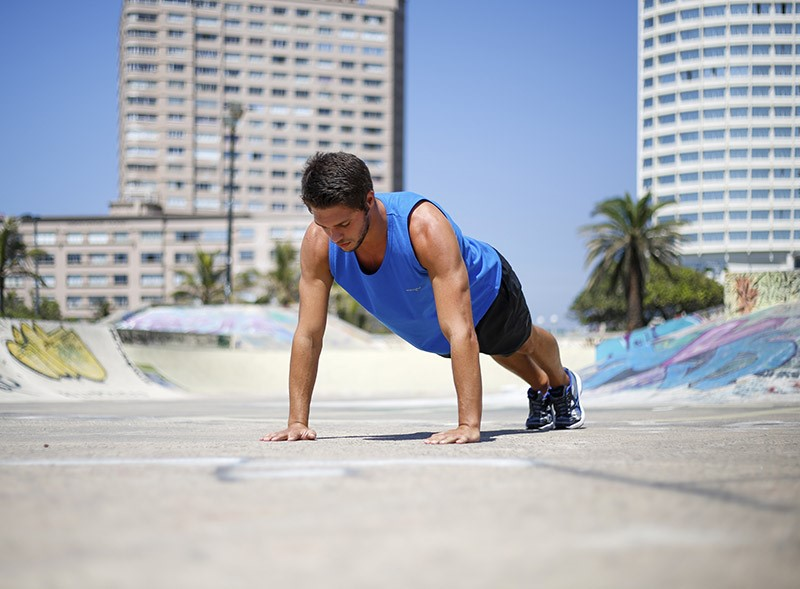 man in blue vest doing a push up exercise