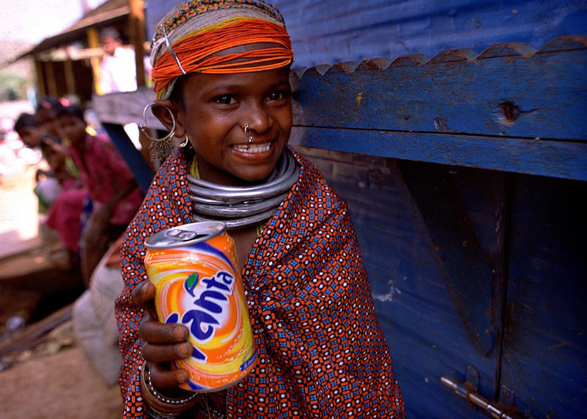 indian girl holding a can of fanta orange