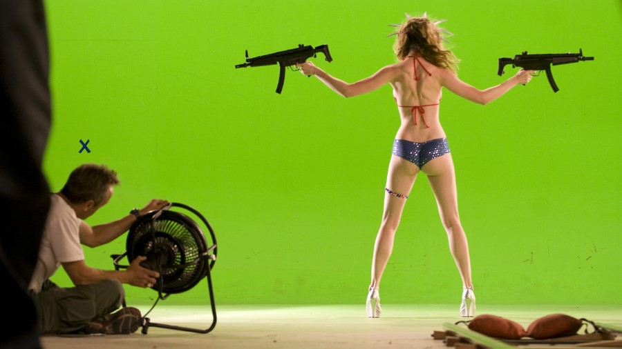 woman in high heels and a bikini armed with machine guns in front of a green screen with a fan