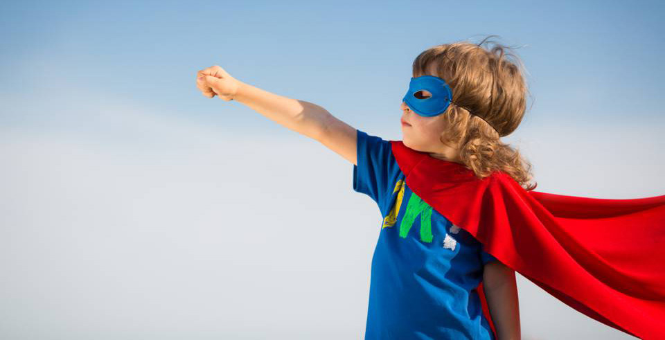 child dressed as a powerful superhero, complete with mask and cape