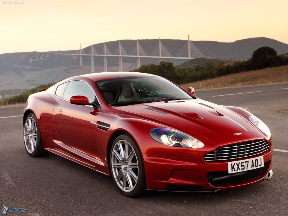 red aston martin dbs in front of millau viaduct cable-stayed bridge in france - tallest in the world 5
